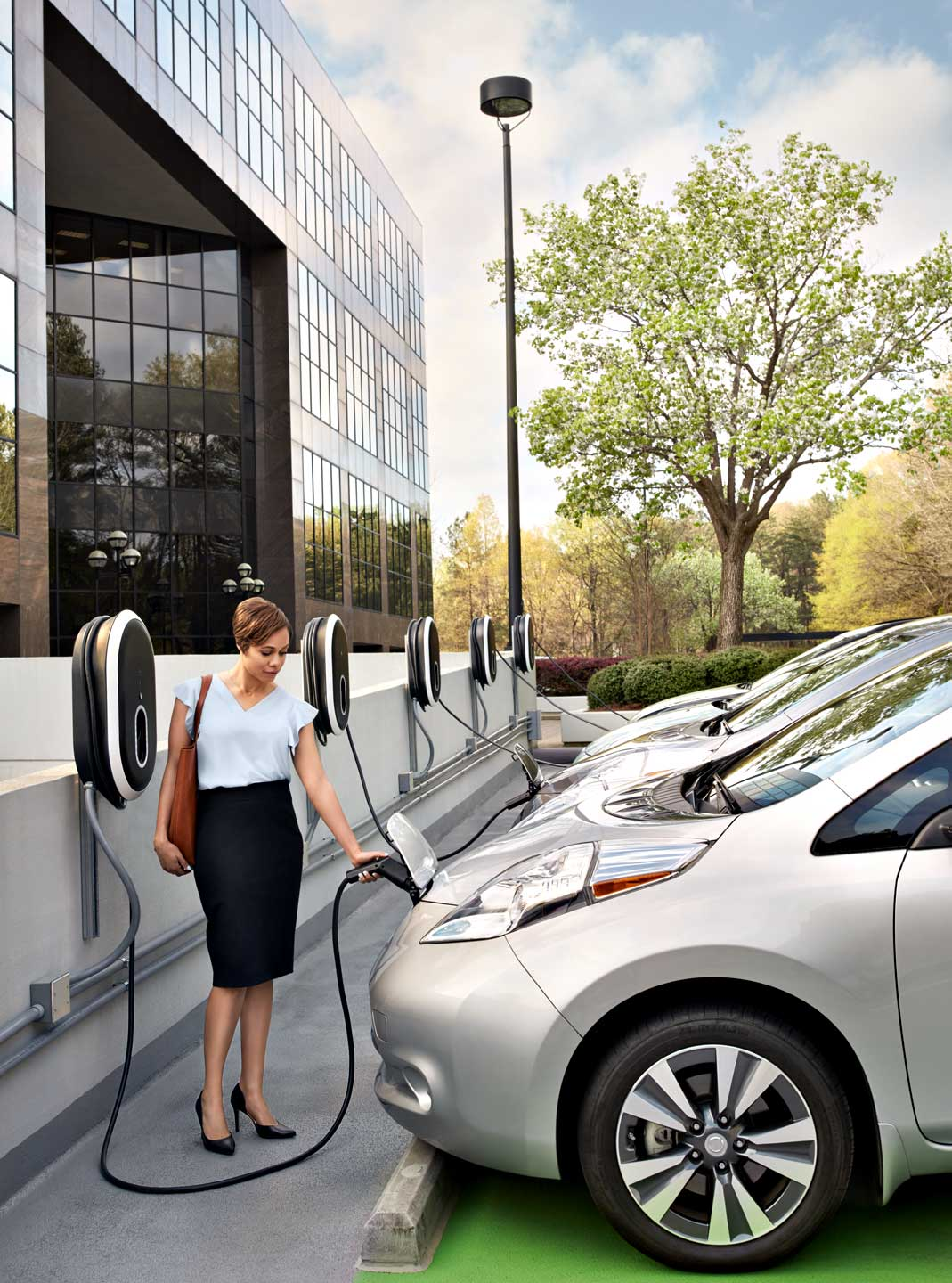 Woman charges electric car at office park, Atlanta. Photographer Nick Burchell