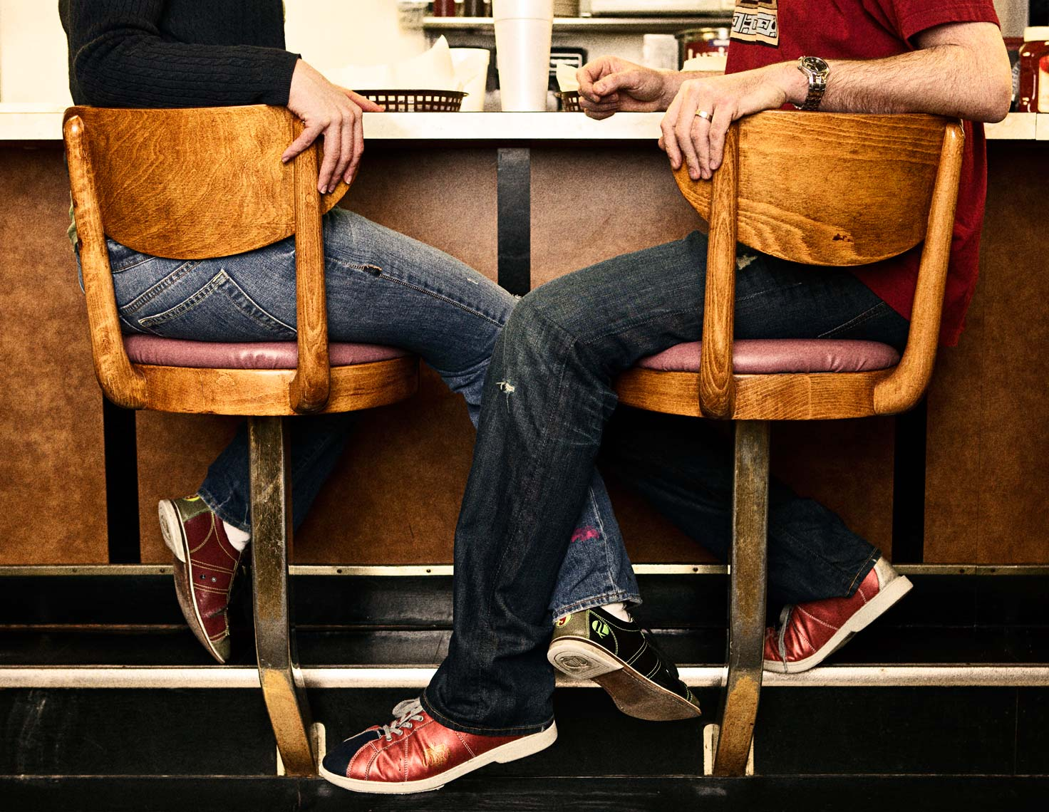 Couple sit on bar stools with legs intertwined. Photography Nick Burchell