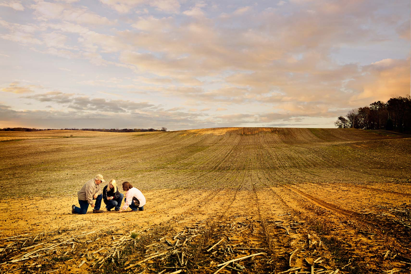 Farmers crouch in field as sun sets by farm photographer Nick Burchell