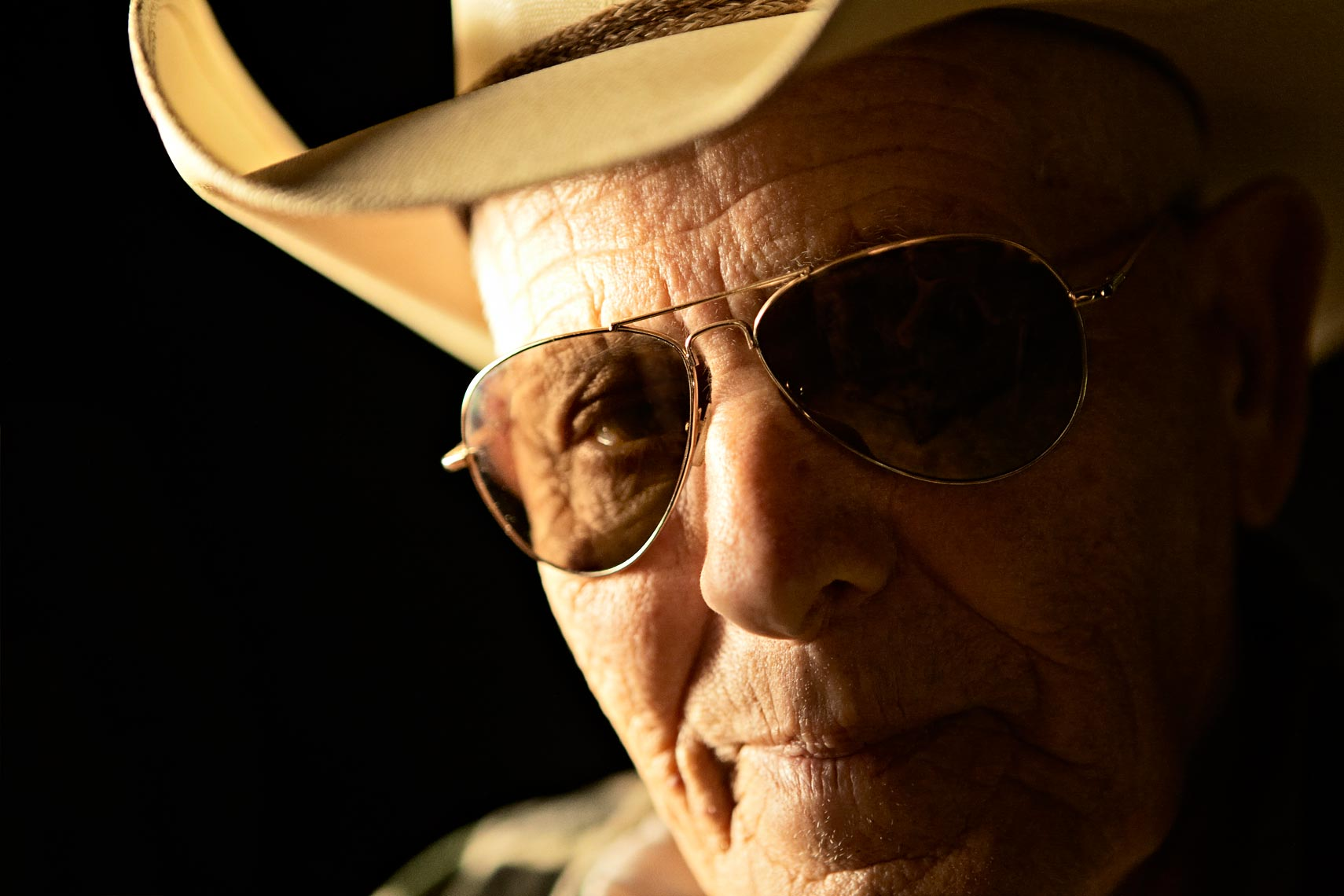Tight portrait of old man wearing cowboy hat and sunglasses at night
