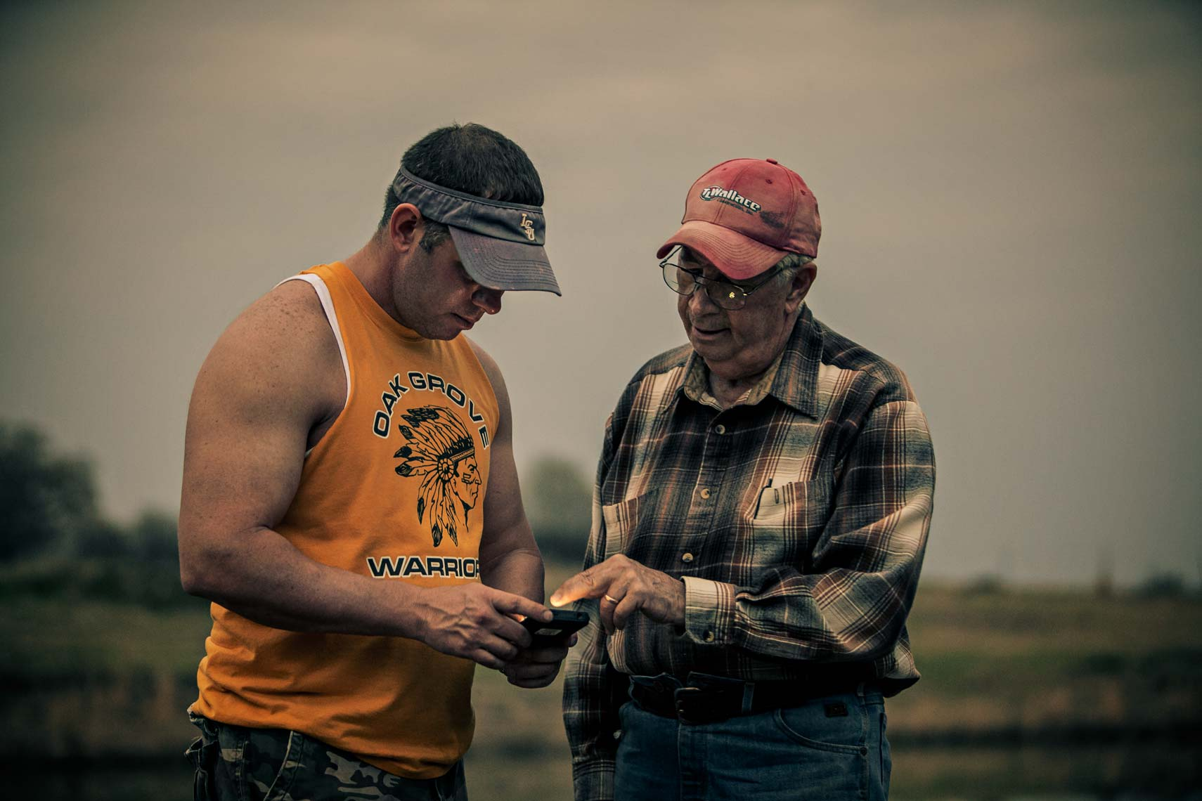 Retired rural man and son check cell phone at dusk. Lifestyle photography