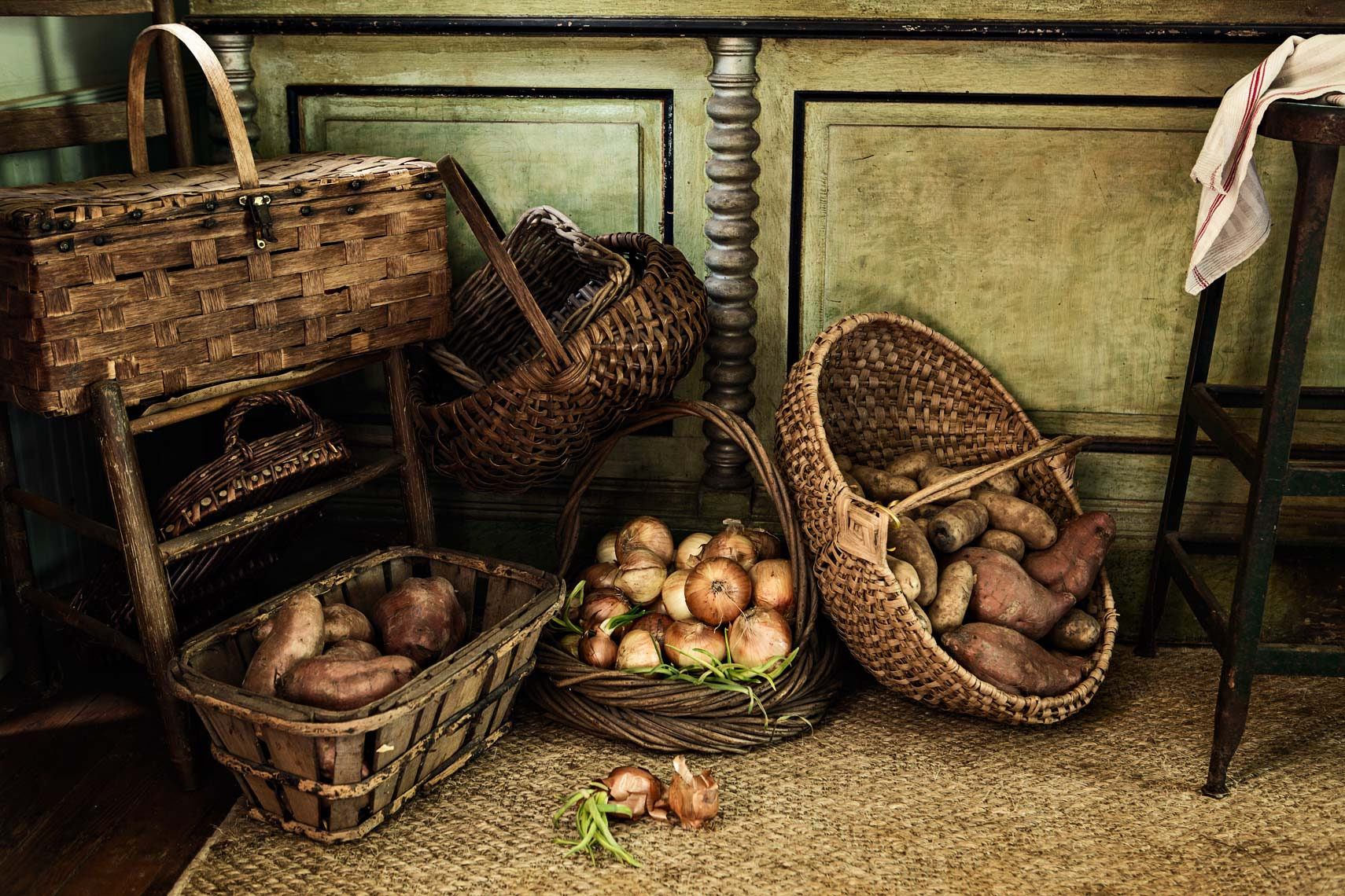 Rustic woven baskets with onions and potatoes rest on kitchen floor, Atlanta
