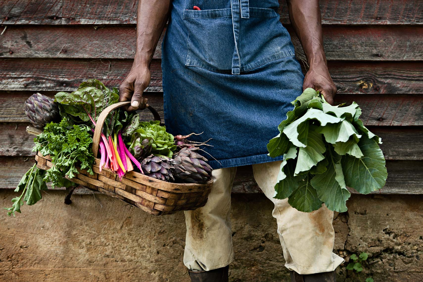 Lifestyle portrait of African American farmer holding basket of vegetables, Atlanta