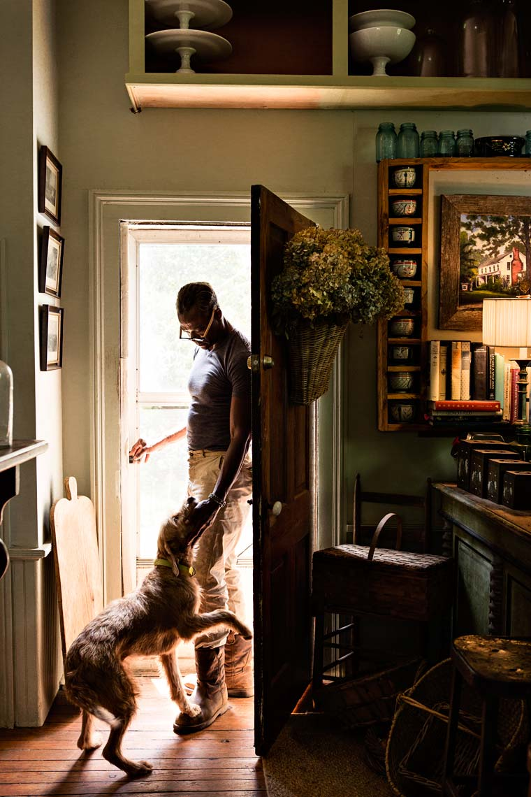 African American man with dog in doorway of home, Atlanta