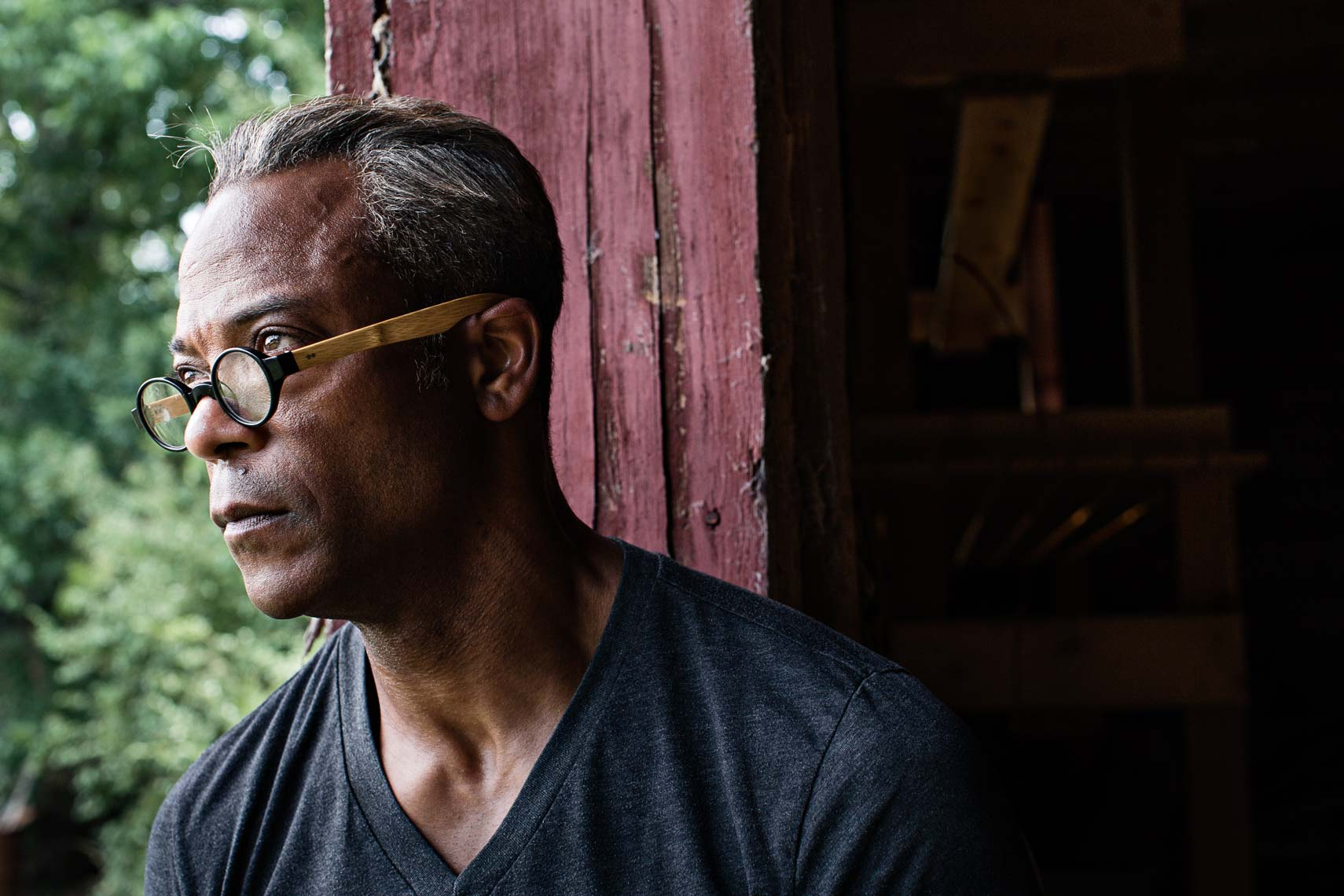 Lifestyle portrait of african american male looking from doorway of barn, by Atlanta based lifestyle photographer