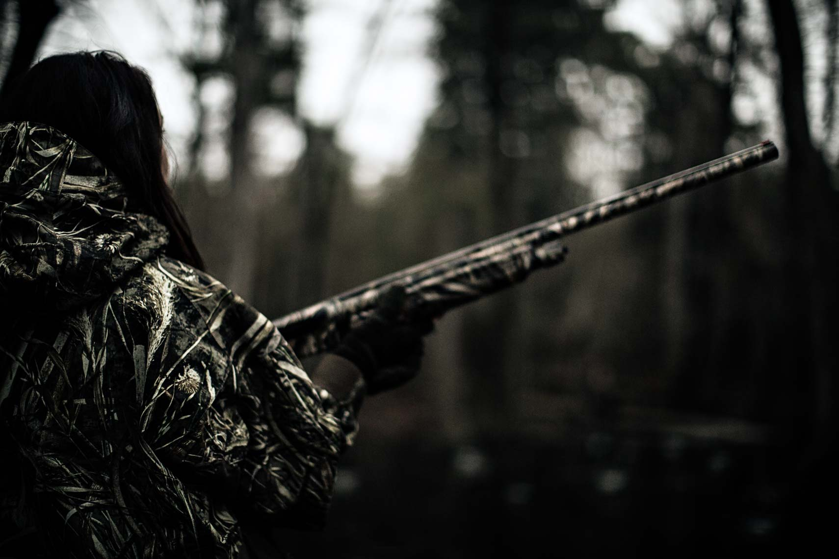 Photograph of female duck hunter with gun by lifestyle photographer Nick Burchell