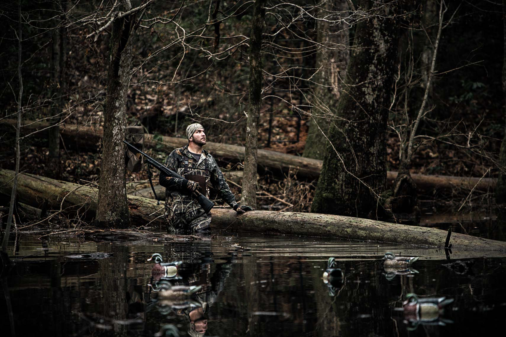 Duck hunter wearing camo gear, standing in pond at dawn. Atlanta photographer