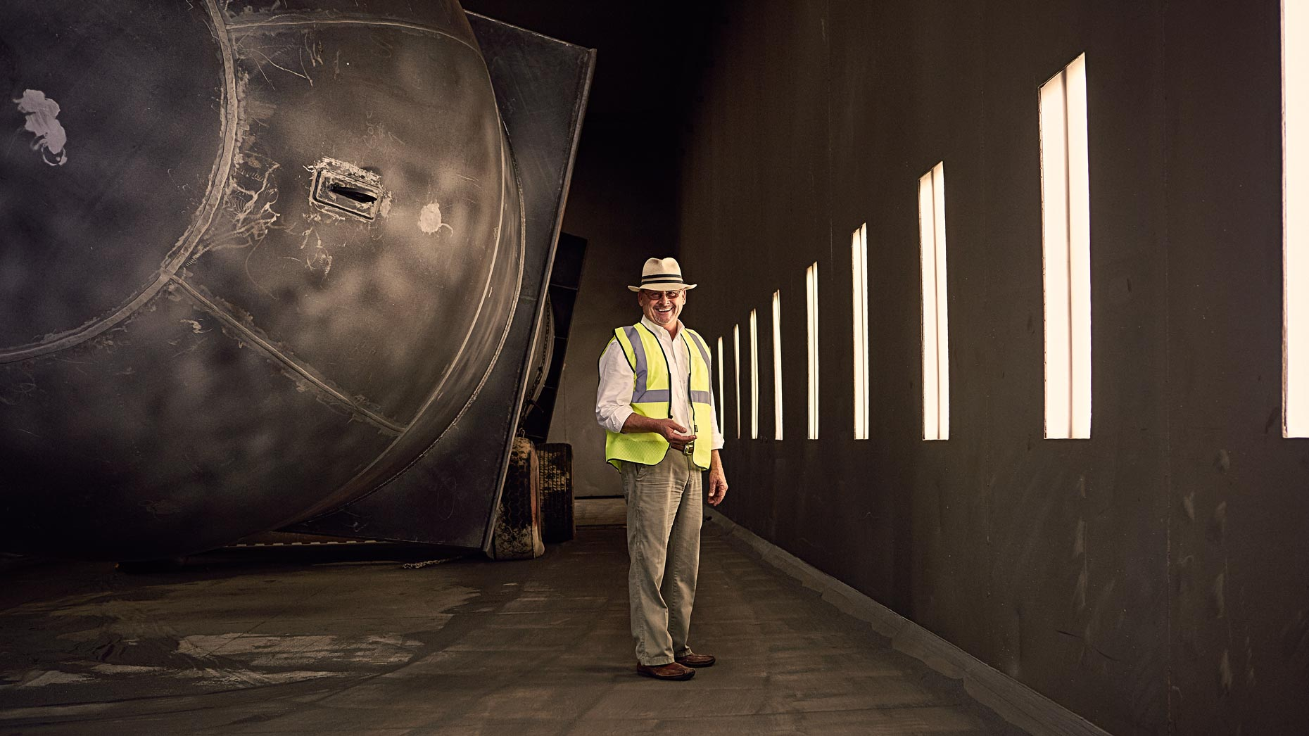 Portrait of man wearing hard hat inside large industrial space, Atlanta