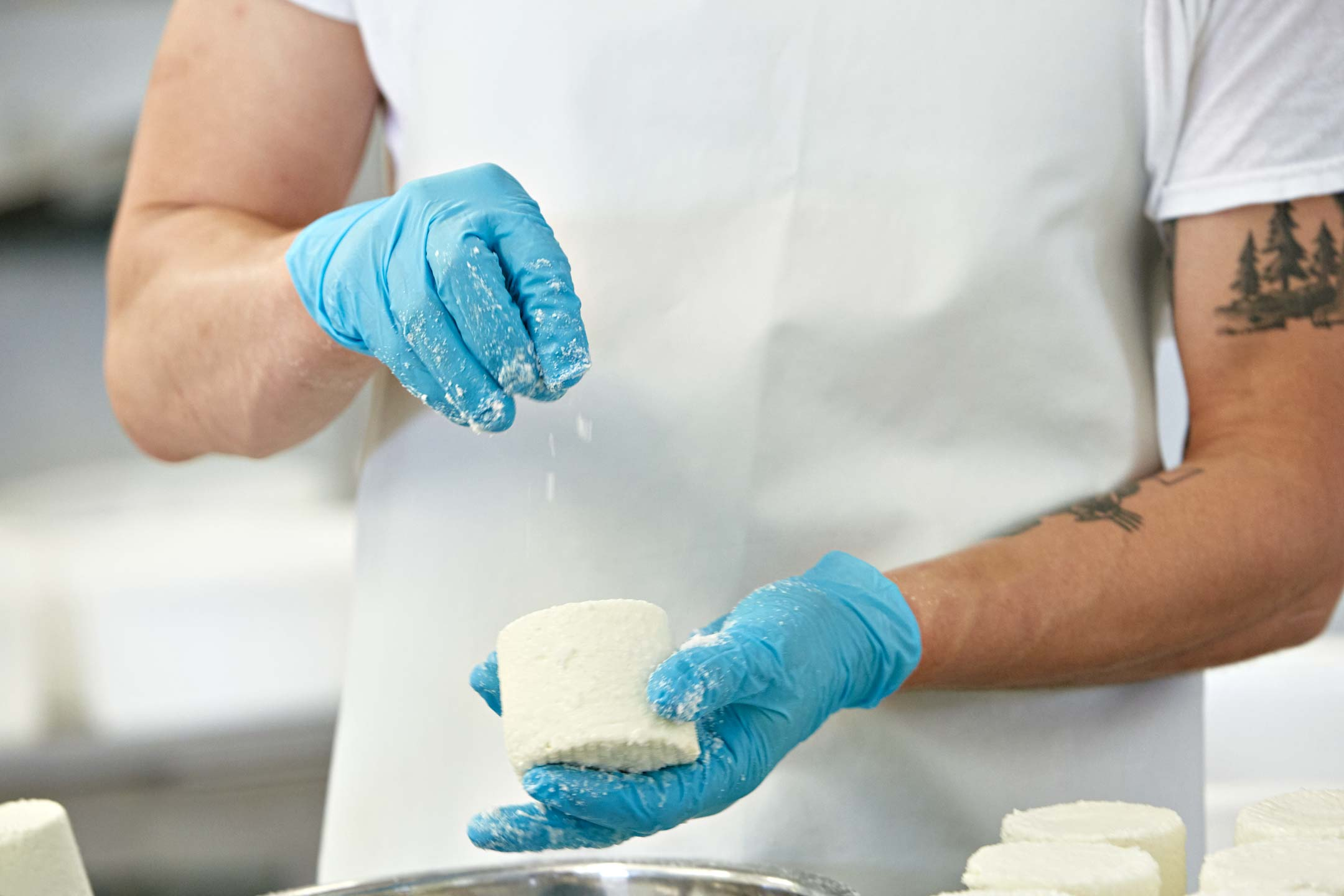 Cheesemaker sprinkles salt on fresh cheese. Atlanta lifestyle photographer