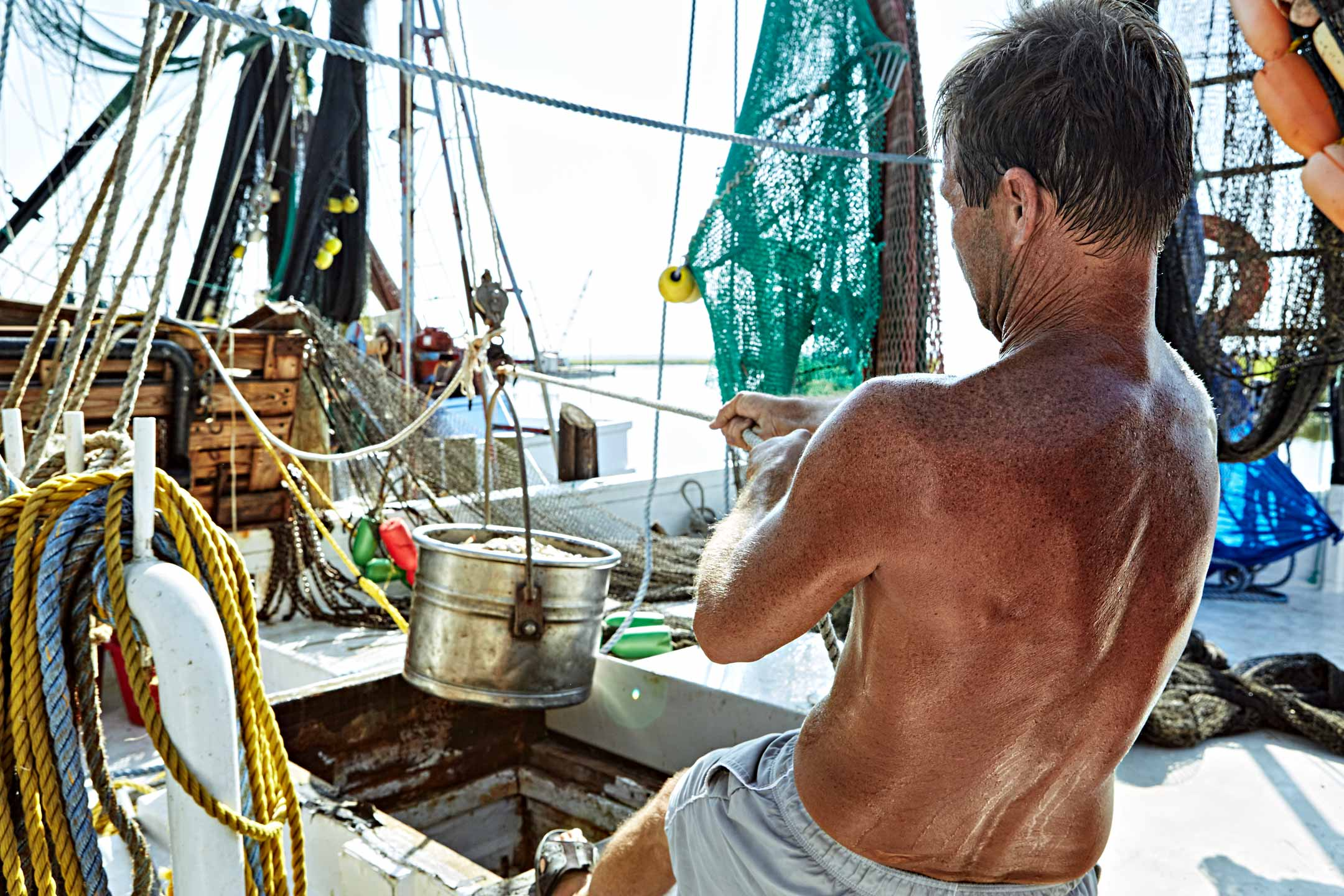 Bare-chested worker pulls on rope, unloading shrimp off boat. Lifestyle photography