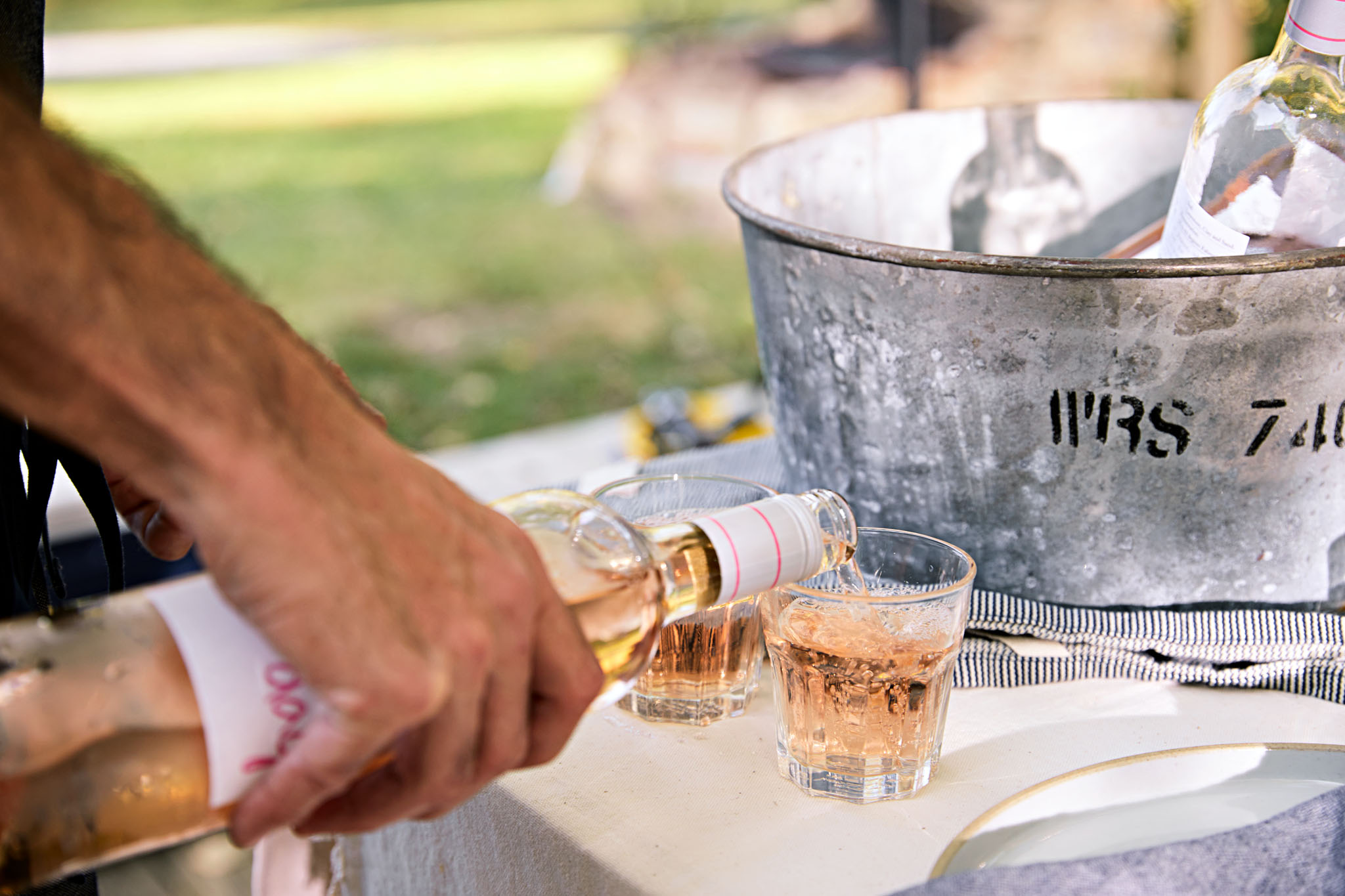 Guest at outdoor party pours rose wine, Atlanta. Photography Nick Burchell