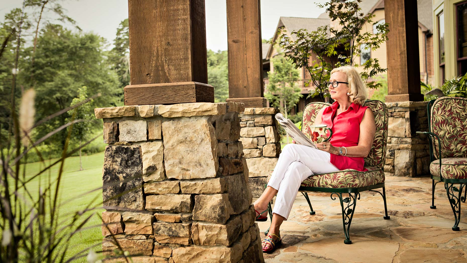 Senior woman sits on her patio looking out at garden, Atlanta